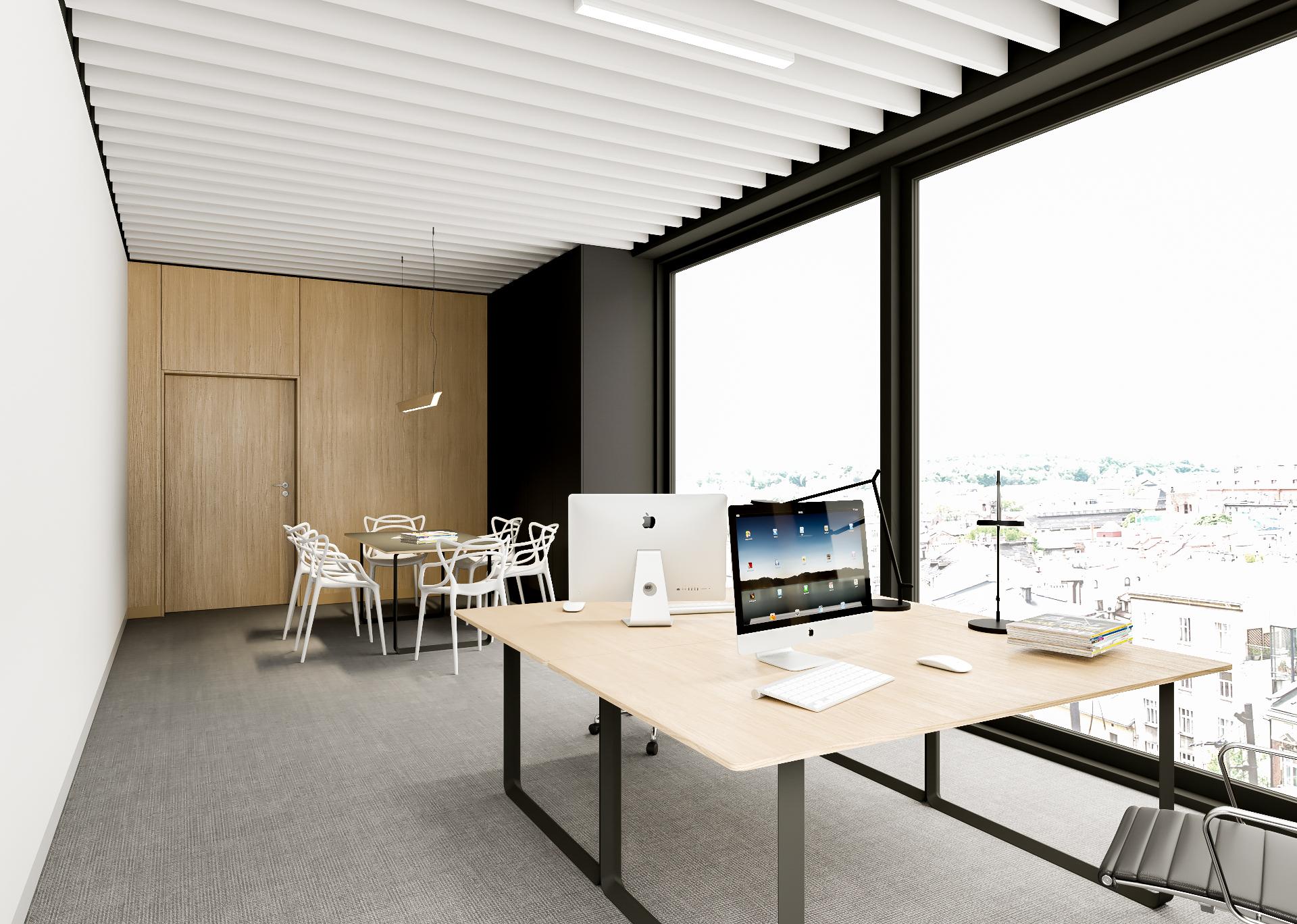 Pokój z dużymi oknami z dwoma biurkami. Na biurkach znajdują się laptopy. W pokoju nie ma osób.